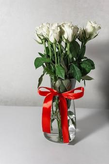 Witte theeroosjes staan in een glazen vaas, die is vastgebonden met een rood lint en op de tafel staat.