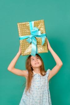 Witte tiener met een blauwe jurk houdt een geschenkdoos boven haar hoofd op een groen oppervlak
