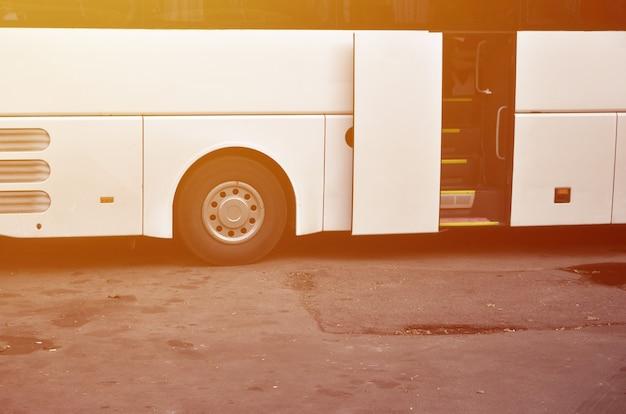 Witte toeristenbus voor excursies. de bus staat geparkeerd op een parkeerplaats in de buurt van het park