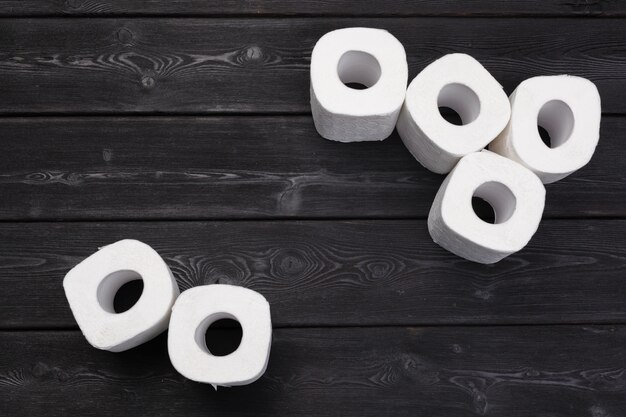 Witte toiletpapierbroodjes op zwarte houten achtergrond