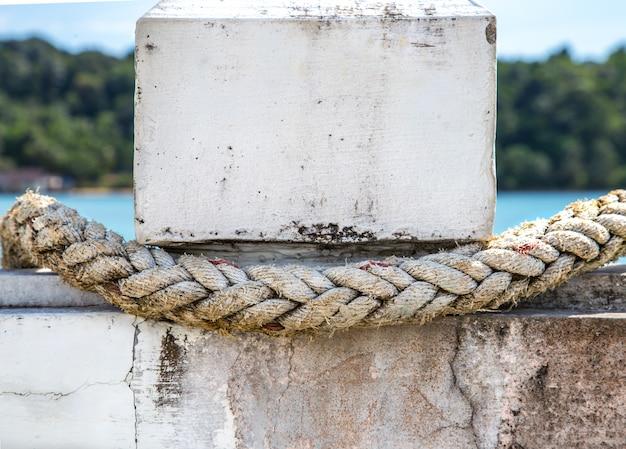 Witte touw close-up, vastgebonden aan de pier