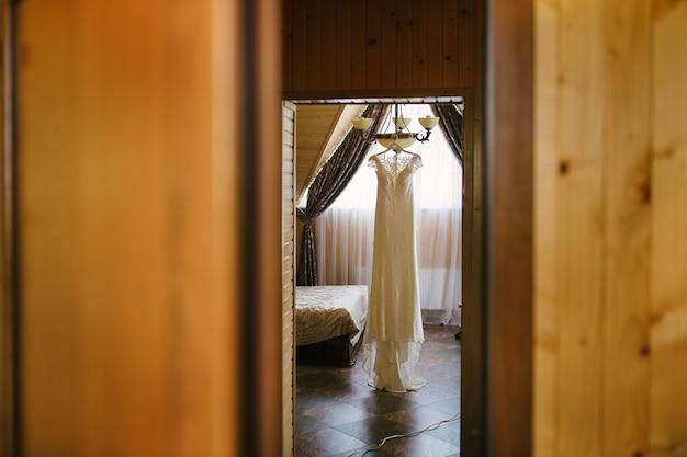 Witte trouwjurk opknoping op een kroonluchter in de kamer
