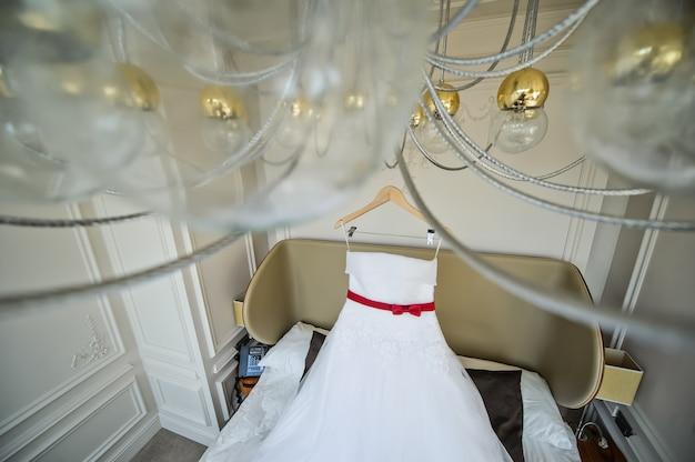 Witte trouwjurk van de bruid die op de kroonluchter in de hotelkamer hangt