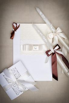 Witte trouwkaart met lint en papier kant. kaarsen met linten