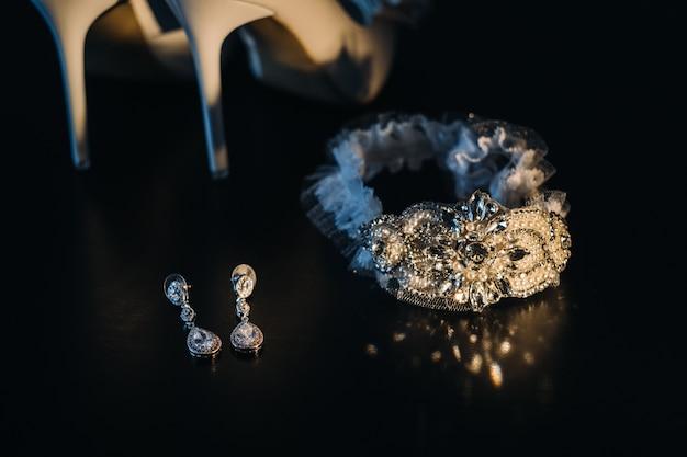 Witte trouwschoenen en jarretellegordel met oorbellen op een zwarte achtergrond