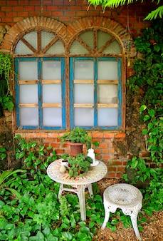 Witte tuintafel en stoel met mini-bloembakken in de achtertuin