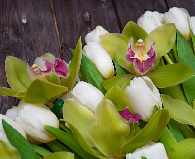 Witte tulpen en groene orchideeën op een donkere houten tafel