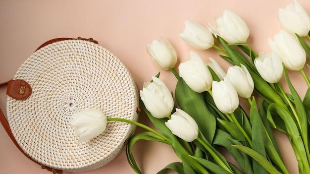 Witte tulpen en rieten ronde dameshandtas op een roze ondergrond, bovenaanzicht