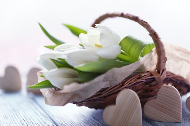 Witte tulpen in een rieten mand op een lichtblauwe tafel