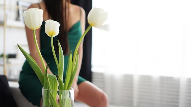 Witte tulpen in een vaas. onscherpe achtergrond - vrouw in een groene jurk. lente vakantie achtergrond.