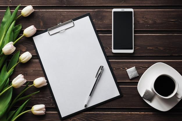 Witte tulpen op een houten tafel met een lege papieren tablet en smartphone en een kopje koffie
