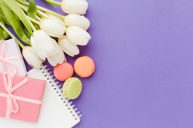 Witte tulpenbloemen en snoep plat