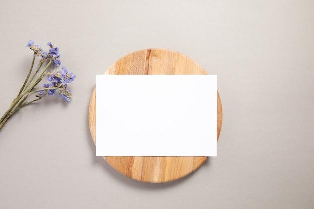 Witte uitnodigingskaart op een hout met paarse bloem