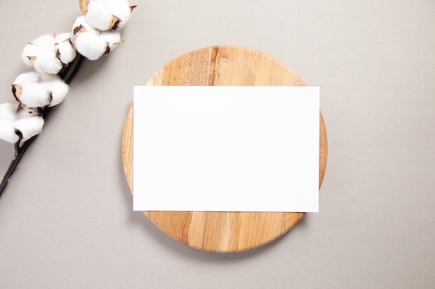 Witte uitnodigingskaart op een houten bord met katoenen tak
