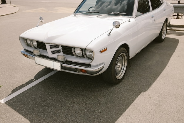 Witte uitstekende retro auto op een parkeren.