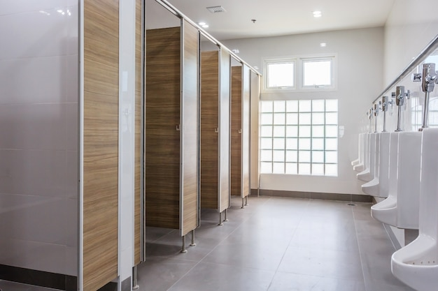 Witte urinoirs in schone mensen openbare toiletruimte leeg met groot venster en licht van buitenkant