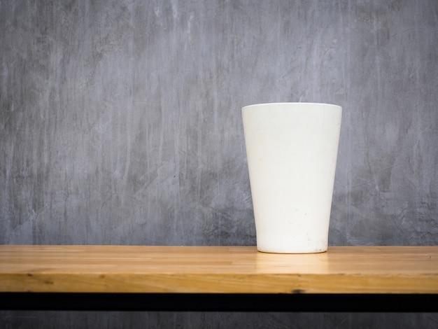 Witte vaas die op een houten bank wordt geplaatst