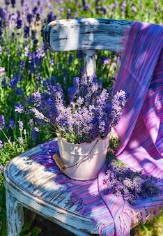Witte vaas met lavendelboeket op vintage stoel
