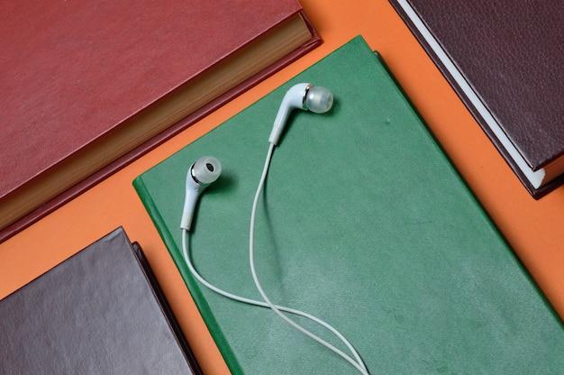 Witte vacuümkoptelefoons liggen op boeken op een oranje achtergrond. audioboek-concept.