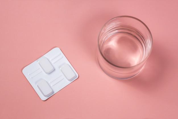 Witte vaginale antibacteriële pillen op roze achtergrond. kaarsen worden gedrenkt in water en geïnjecteerd in de vagina om candidiasis, spruw, ontsteking te behandelen. effectief modern medicijn voor de behandeling van ziekten