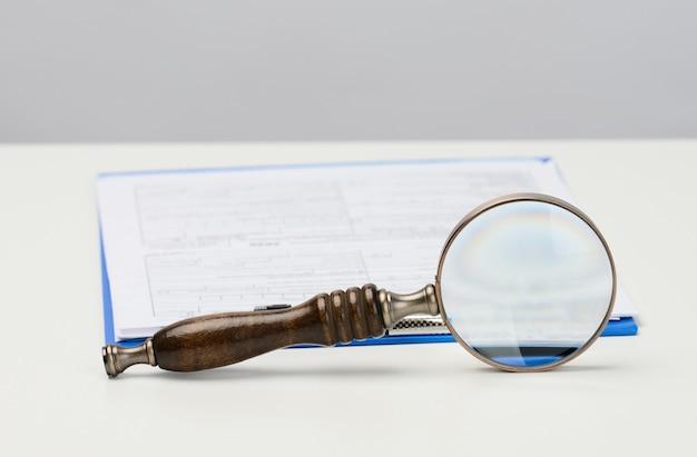 Witte vellen papier en een houten vergrootglas op een witte achtergrond, zoek naar oplossingen en antwoorden