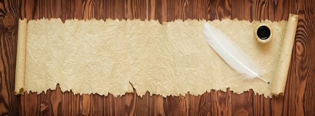 Witte veren met oud papier op tafel, panoramisch uitzicht