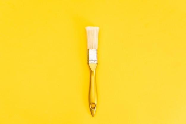 Witte verf kan met borstel bovenaanzicht op gele achtergrond.