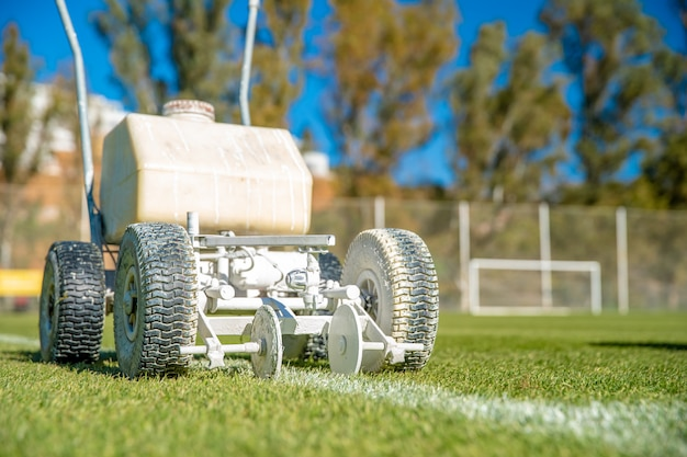 Witte verf op het gras spatten om de machine te helpen de grenzen van een voetbalveld te markeren.