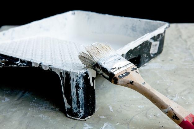 Witte verf, penseel en bakje, voor het schilderen van wit plafond of sierlijsten.