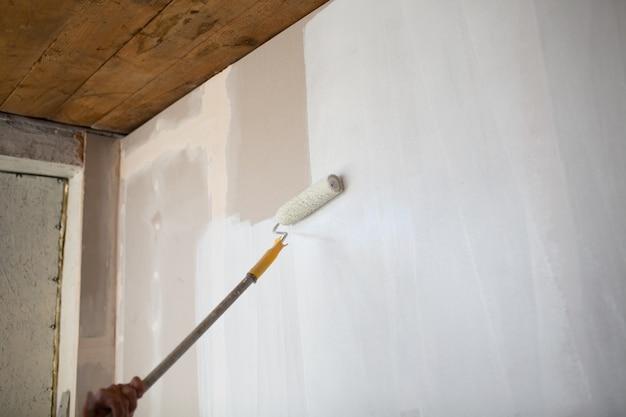 Witte verfroller in de hand met gipsplaten muur.