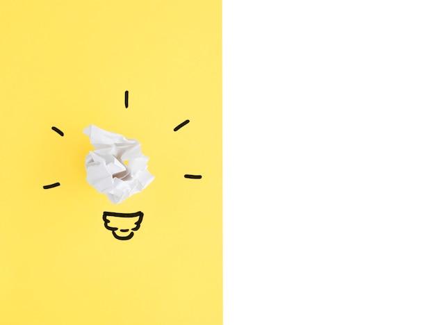 Witte verfrommelde papieren bal gloeilamp op gele en witte achtergrond