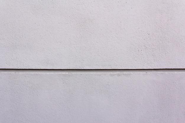Witte verftextuur op de muur met een streep in het midden en ruimte voor tekst.