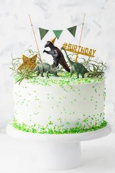 Witte verjaardagstaart met groene decoraties, gouden ster en dinosaurussen op een taartstandaard
