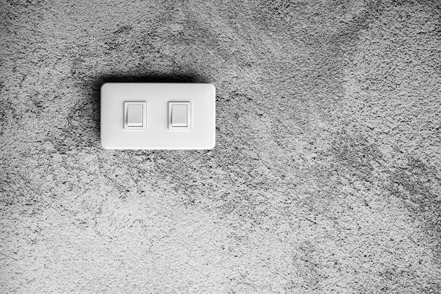 Witte verlichtingsschakelaar bij concrete muur.