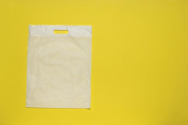 Witte verpakkingstas op een gele achtergrond.