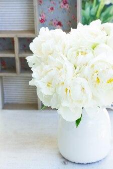 Witte verse bloeiende pioenroos bloemen in vaas op tafel