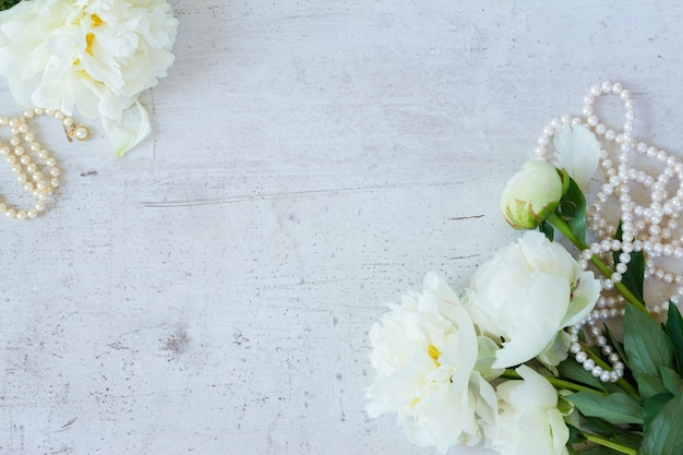 Witte verse pioenroos bloemen met parels sieraden op witte houten achtergrond frame