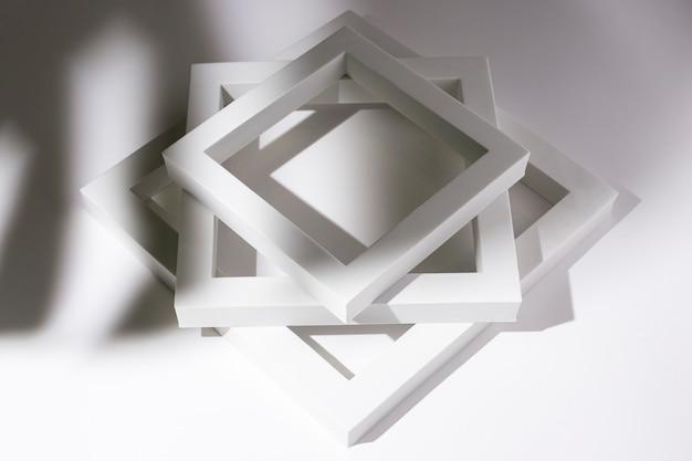 Witte vierkante frames podia voor presentatie in de schaduw van een tropisch blad op een witte achtergrond.