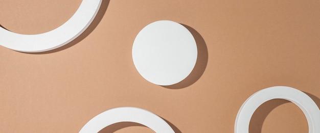 Witte vierkante geometrische presentatiepodia op bruine achtergrond. bovenaanzicht, plat gelegd. banier.