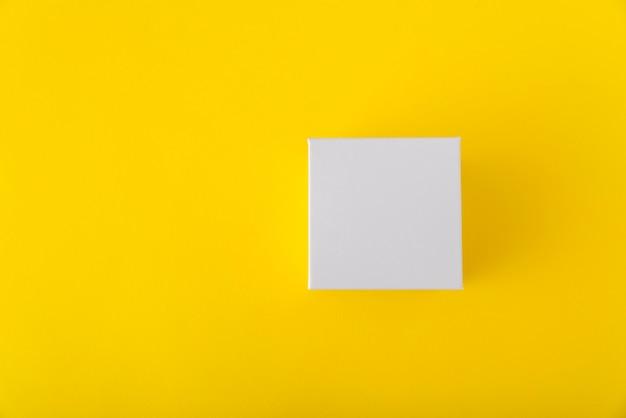 Witte vierkante kartonnen doos op gele achtergrond. kopieer ruimte. bespotten.