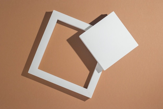 Witte vierkante podia voor presentaties op een bruine achtergrond. bovenaanzicht, plat gelegd.
