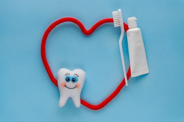 Witte vilttand met tandpasta en tandenborstel op blauwe achtergrond.