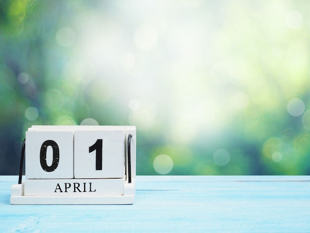 Witte vintage houtblok kalender huidige datum 01 en maand april op blauwe houten tafel over abstracte groene bokeh achtergrond met kopie ruimte.