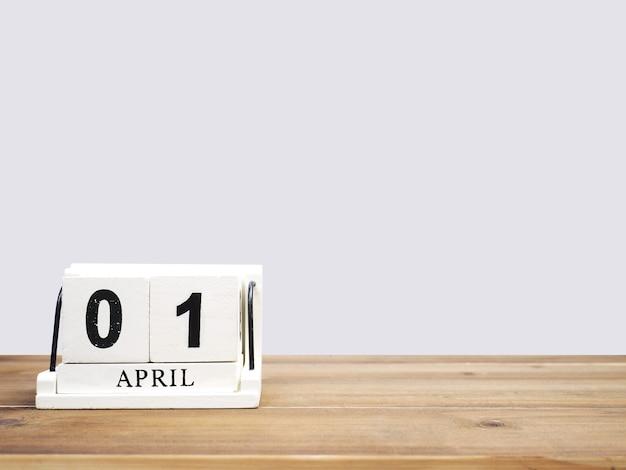Witte vintage houten blok kalender huidige datum 01 en maand april op bruine houten tafel over grijze achtergrond met kopie ruimte.