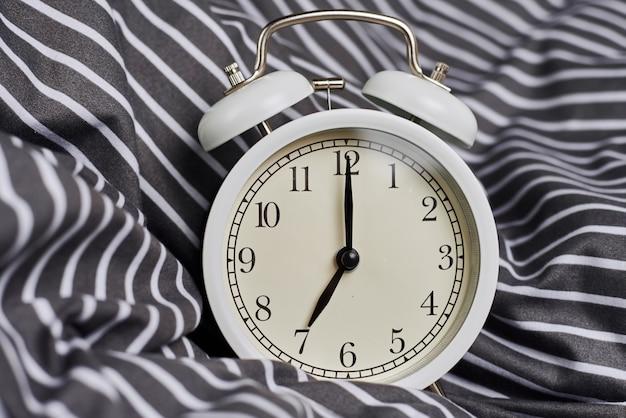 Witte vintage wekker op kussen in bed. wale up en morning concept