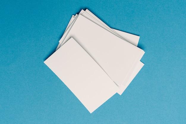 Witte visitekaartjes op kantoor op blauw glas bovenaanzicht mockup
