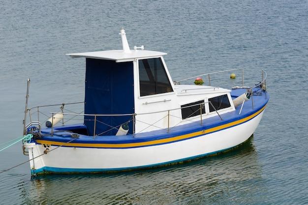 Witte vissersboot met motor voor anker in de zee