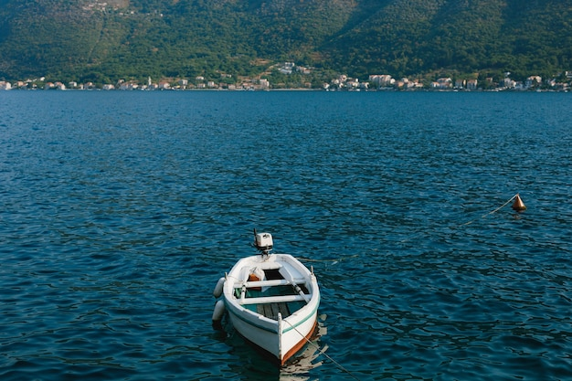 Witte vissersboot op het water in de buurt van de bergen van de stad perast