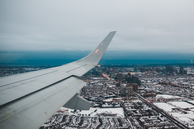 Witte vliegtuigvleugel over stad overdag