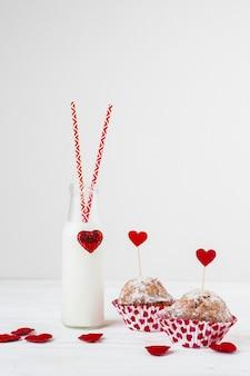 Witte vloeistof in fles met buizen dichtbij cakes met hart op toverstokjes